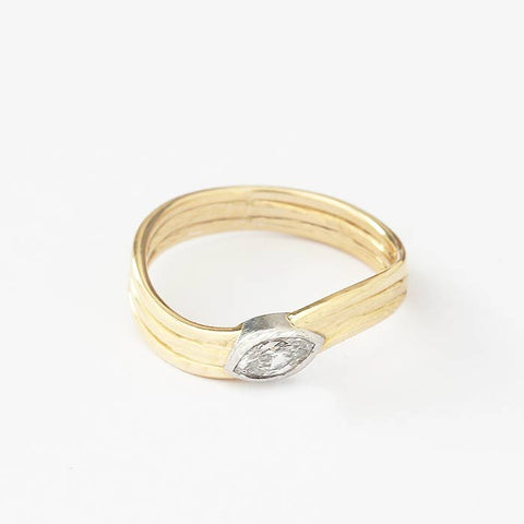 a modern secondhand marquise cut diamond single stone ring with a white gold rub over setting and yellow 3 grooved band