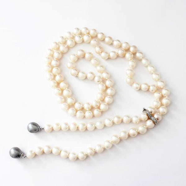 a uniform set of freshwater pearls in a necklace with white gold settings and a white diamond separator attachment and 2 grey pearls at the end