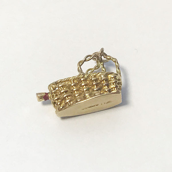 a yellow gold vintage charm with a bottle of wine inside