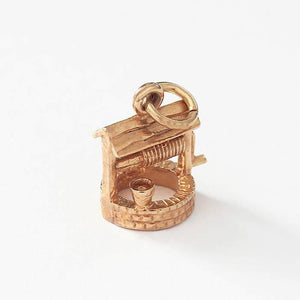 a vintage wishing well charm in yellow gold