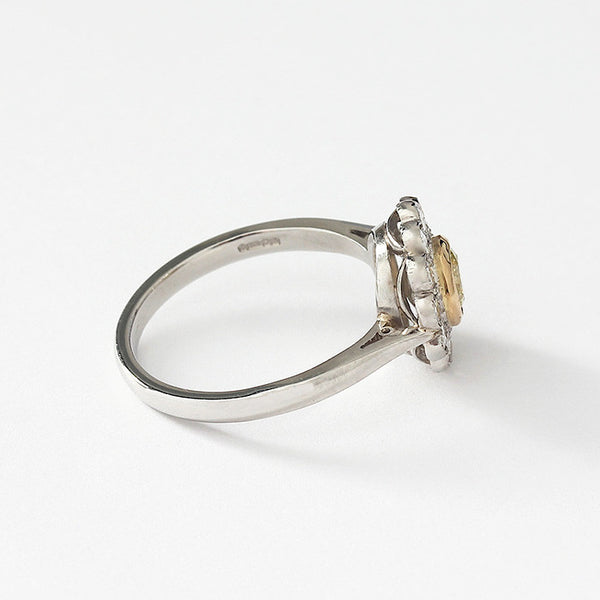 a platinum diamond cluster daisy ring with yellow diamond centre stone
