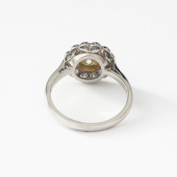 a platinum diamond cluster daisy ring with a yellow diamond in the centre all rub-over set