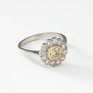 a diamond cluster with a central yellow diamond round and platinum mount