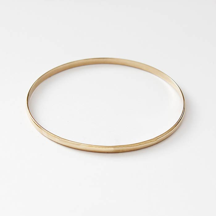 a secondhand plain solid round gold bangle in 18 carat yellow with a full hallmark