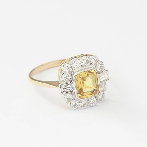 a secondhand yellow rectangular sapphire and diamond cluster in a rub-over setting in white and yellow gold band