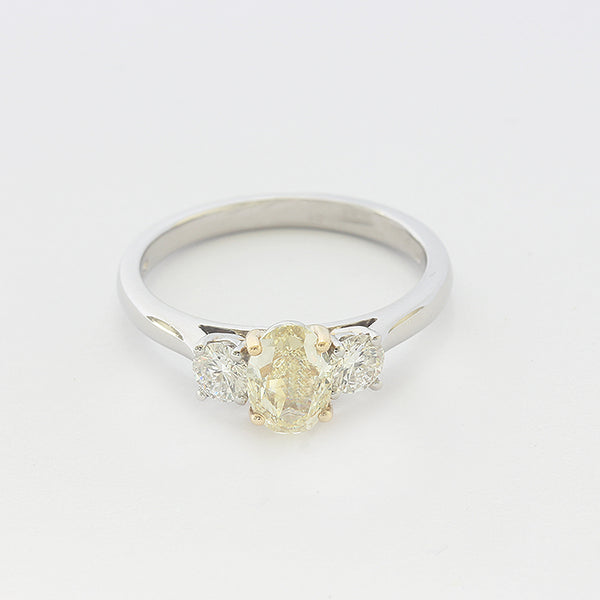 a platinum diamond 3 stone ring with central yellow diamond