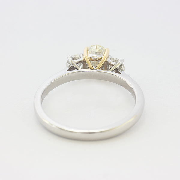 a platinum 3 stone ring with central oval yellow diamond