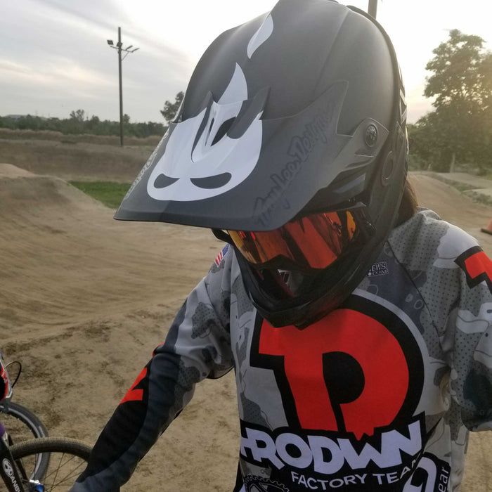 Nag #1 Factory Throdwn's Ava Corley, rocking her Danger Snacks official flame logo helmet sticker installed on her Fly helmet, at Whittier Narrows BMX