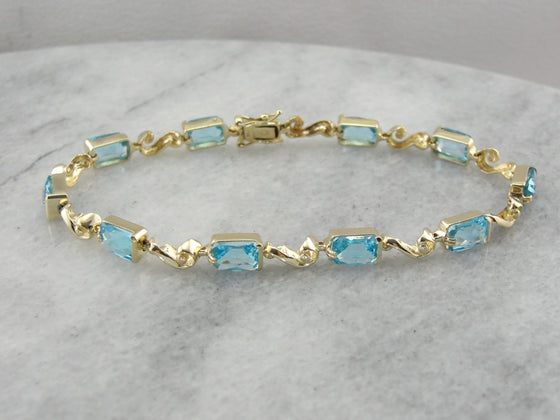 Bright Blue Topaz Gemstone Tennis Bracelet with Decorative Gold Links