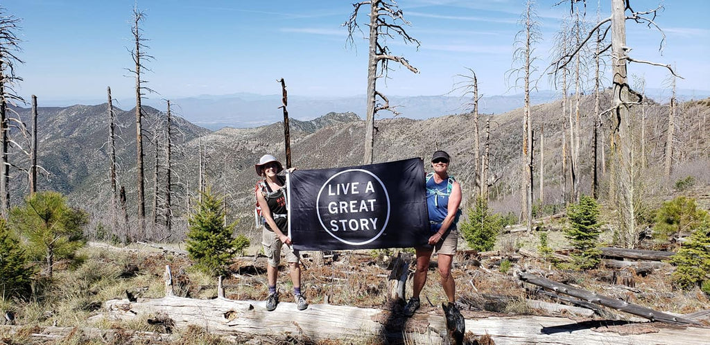 LIVE A GREAT STORY flag out in the world adventuring in the mountains