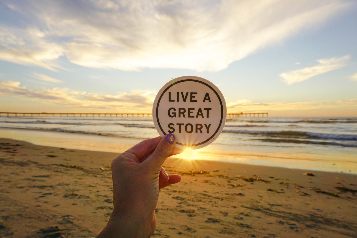 Girl with Cute Nails holding inspiring LIVE A GREAT STORY Sticker at the Beach in California