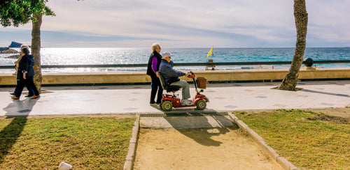 elderly man on mobility scooter along the water