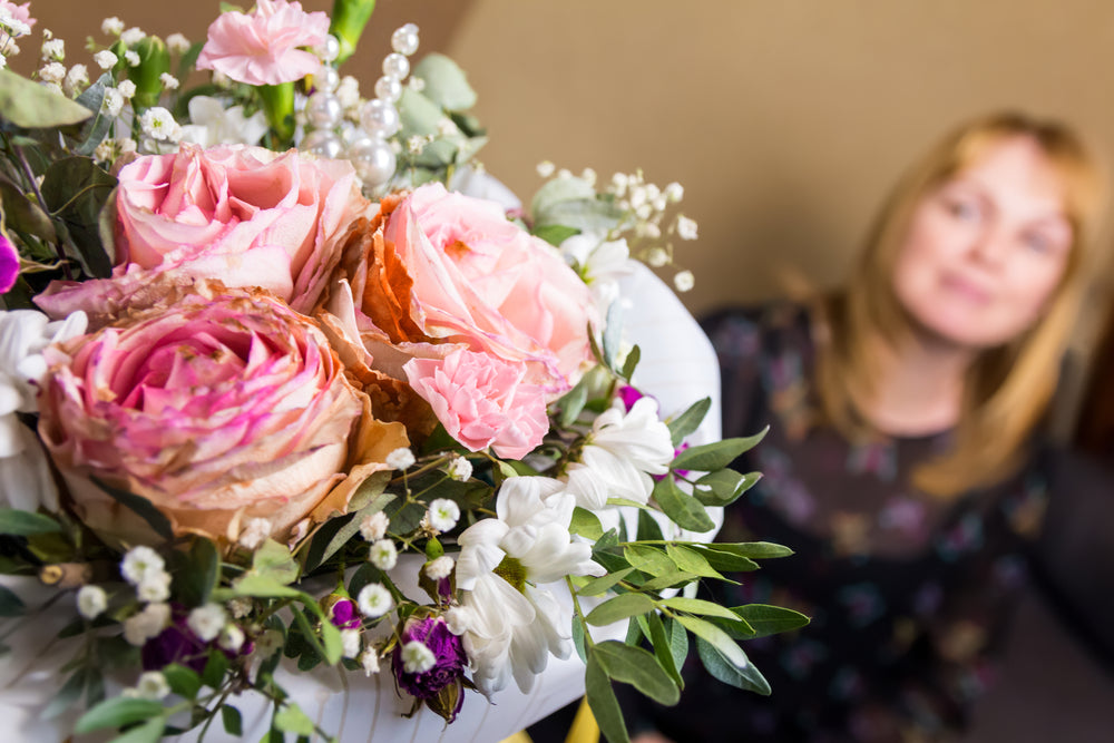 woman receiving flowers for mother's day
