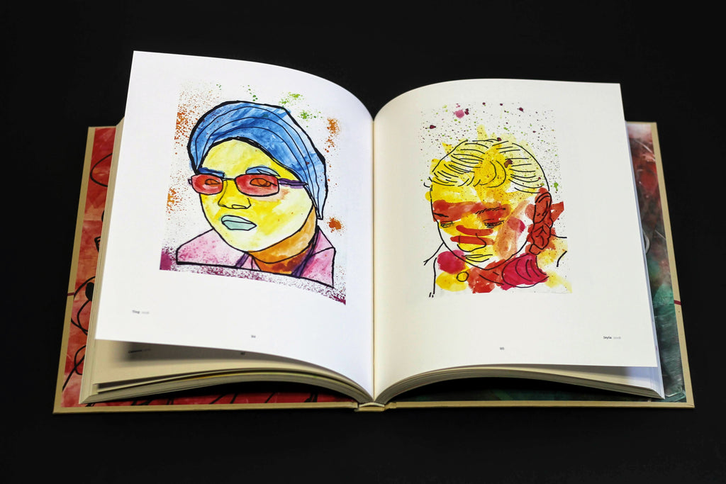 A book sits open on a dark surface. The displayed spread shows two portraits by two different artists.