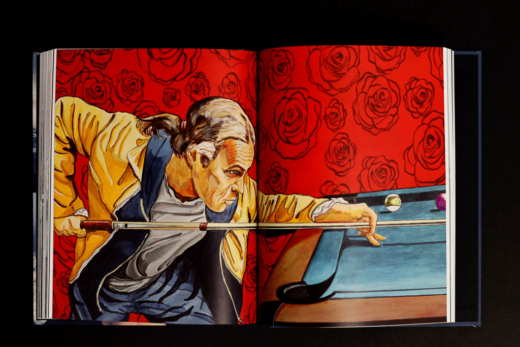 A book sits open on a dark surface. The displayed spread shows an illustrated spread of a man playing pool.