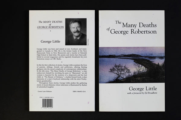 Two books, both The Many Deaths of George Robertson, sit side-by-side on a black surface, one is face up and the other is face down.
