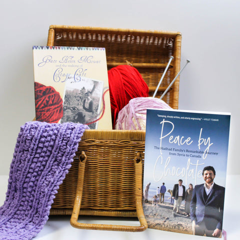 A basket sits open, revealing balls of yarn and a book, Grace Helen Mowat and the Making of Cottage Craft, and a knitted piece spills out of the side. A book, Peace by Chocolate, stands in front of the basket.