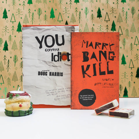 Two books, YOU comma Idiot and MARRY, BANG, KILL, stand up against a backdrop patterned with shiny, green trees. In front of the books sits a tealight in a holder shaped like a snowman's head and two weathered matchboxes.