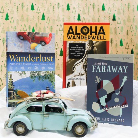 Three books, Wanderlust, Aloha Wanderwell, and a Song from Faraway, stand against a backdrop patterned with shiny, green trees. White tissue paper covers the ground, made to look like mounds of snow. In the foreground sits a blue toy car that has a life preserver and surfboard on strapped to the roof.