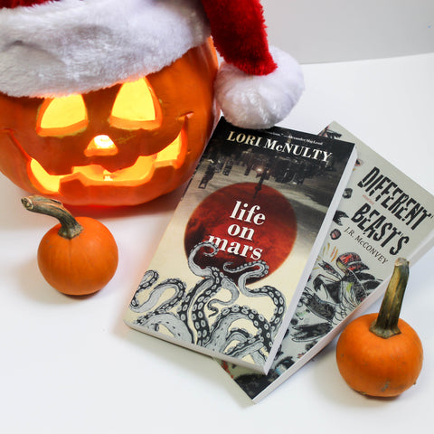 Two books, Life on Mars and Different Beasts, lie partially atop one another next to two tiny pumpkin. A jack-o-lantern with a crooked smile and a fuzzy Santa hat looms in the background.