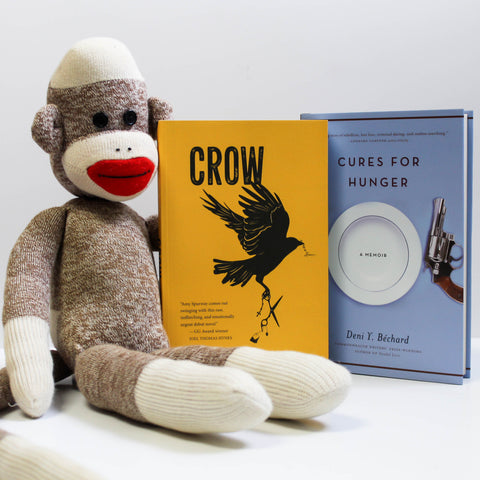 Two books, Crow and Cures for Hunger, stand upright. A sock monkey sits to the left of the books with one arm behind them.