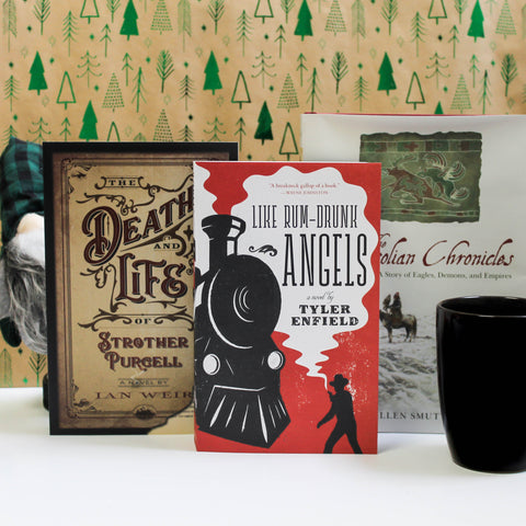 Three books, The Death and Life of Strother Purcell, Like Rum-Drunk Angels, and The Mongolian Chronicles, stand upright in a row against a backdrop patterned with shiny, green trees. A black mug stands in the foreground to the right, and to the left a Yule gnome with a bushy, grey beard peaks out from behind on of the books.