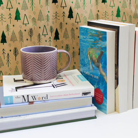 A stack of books lies on a white surface, a pink mug sits atop them, and a row of books stands to the right against a backdrop patterned with shiny, green trees. Only one book in each of the stacks faces towards the camera, The M Word and Catch My Drift.