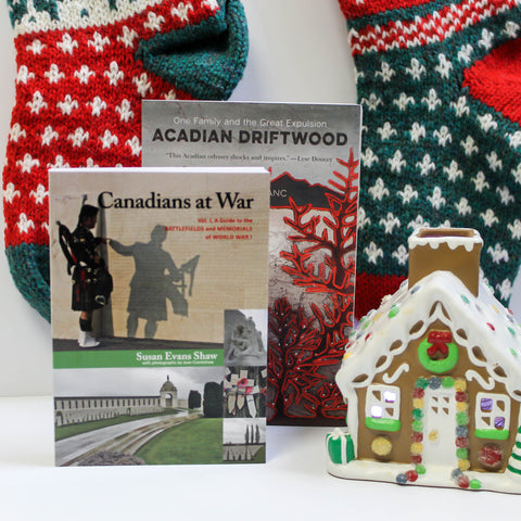 A book, Acadian Driftwood, stands with another book, Canadians at War, Vol. 1, standing in front of it, slightly obscuring it from view. Next to the books sits a gingerbread house. Two knitted stockings hang in the background.