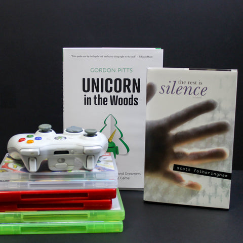 A white Xbox 360 controller sits on top of a stack of green, red, and white video game cases. Two books, Unicorn in the Woods and The Rest of Silence, stand to the right.