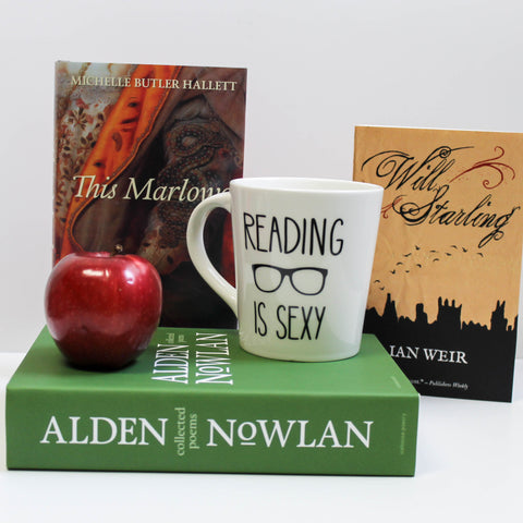 A large green book, Collected Poems of Alden Nowlan, lies on its side and a shiny, red apple and a white mug sit atop it. Two books stand in the back, This Marlowe and Will Starling.