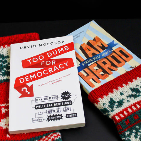 Two knited stockings sit side-by-side on a black surface. A book, Too Dumb for Democracy, sits atop the stocking on the left and another book, I Am Herod, peaks out of the other stocking.