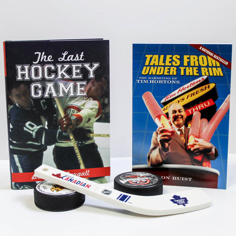 Two books, The Last Hockey Game and Tales from Under the Rim, stand in the background. In front of them sits two hockey pucks with a small, plastic hockey stick leaning against them.