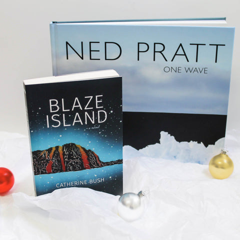 Two books, Blaze Island and Ned Pratt, stand upright amongst scattered ornaments on a bed of crumpled, white tissue paper made to look like mounds of snow.