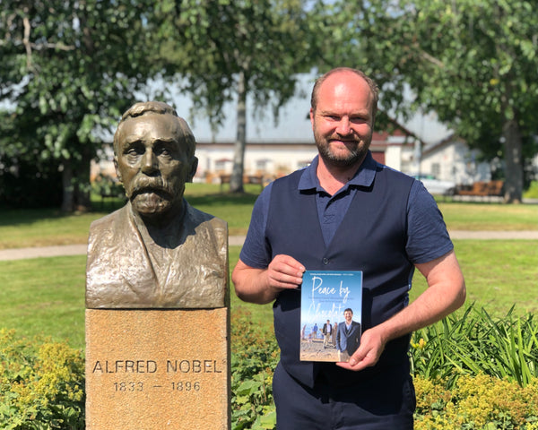 A man holding a copy of Peace by Chocolate stands next to a bust of Alfred Nobel.