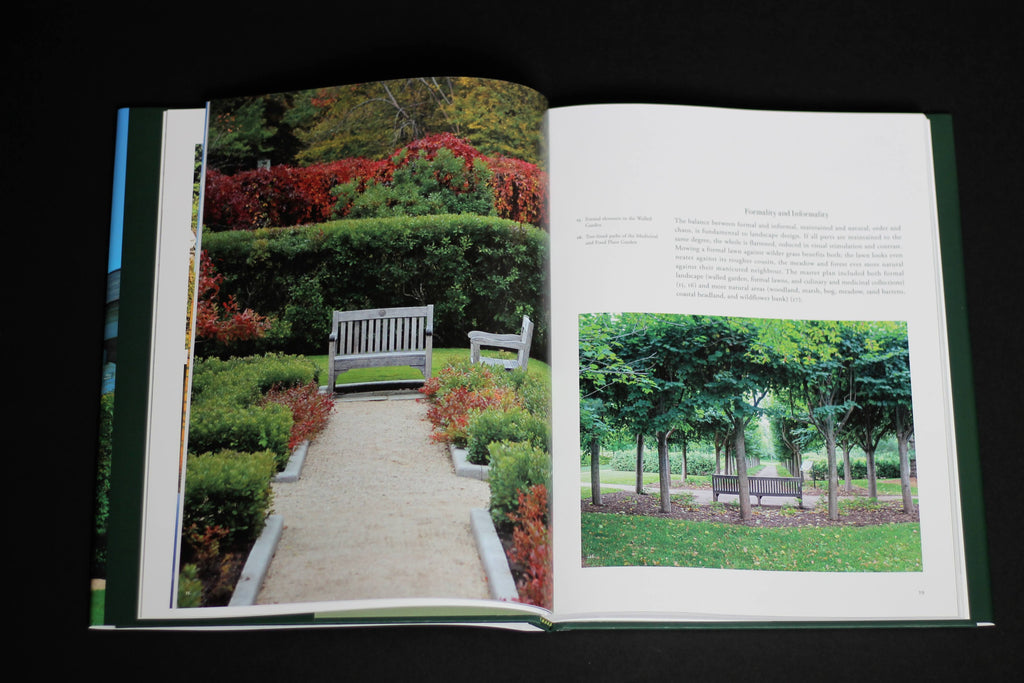 A book sits open on a dark surface. There is a full-page photo of a white bench at the end of a garden path, surrounded by rich green and red foliage. On the other page, there is some text and a smaller photo of a bench along a path, surrounded by young trees.