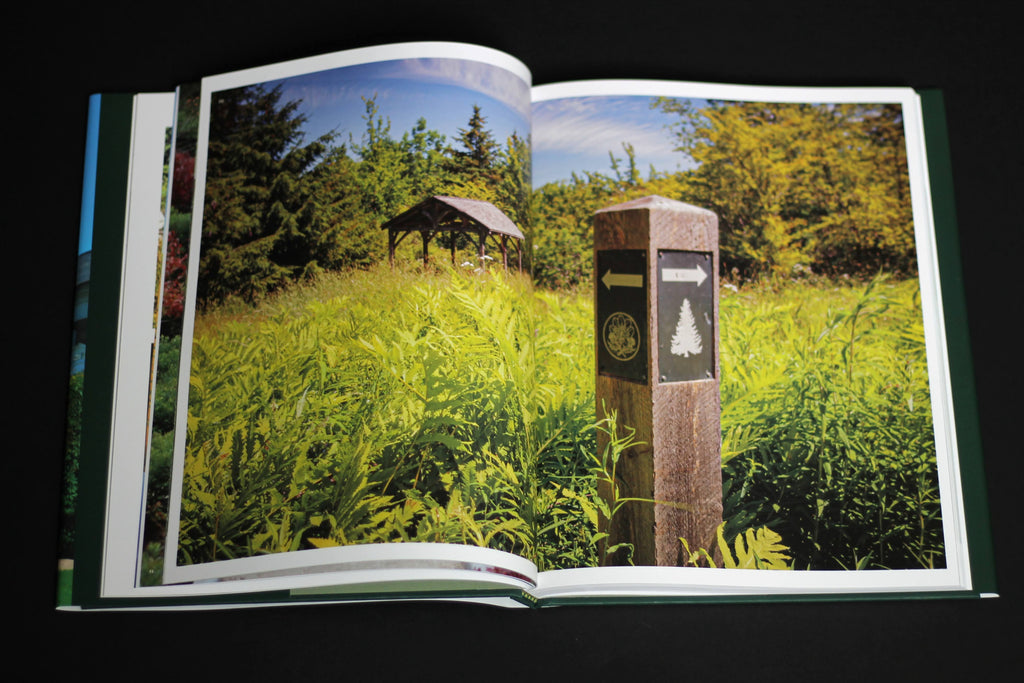 A book sits open on a dark surface. It shows a photo of a lush landscape, overgrown with tall, green brush. There is a trail marker in the forefront and a square gazebo in the distance.