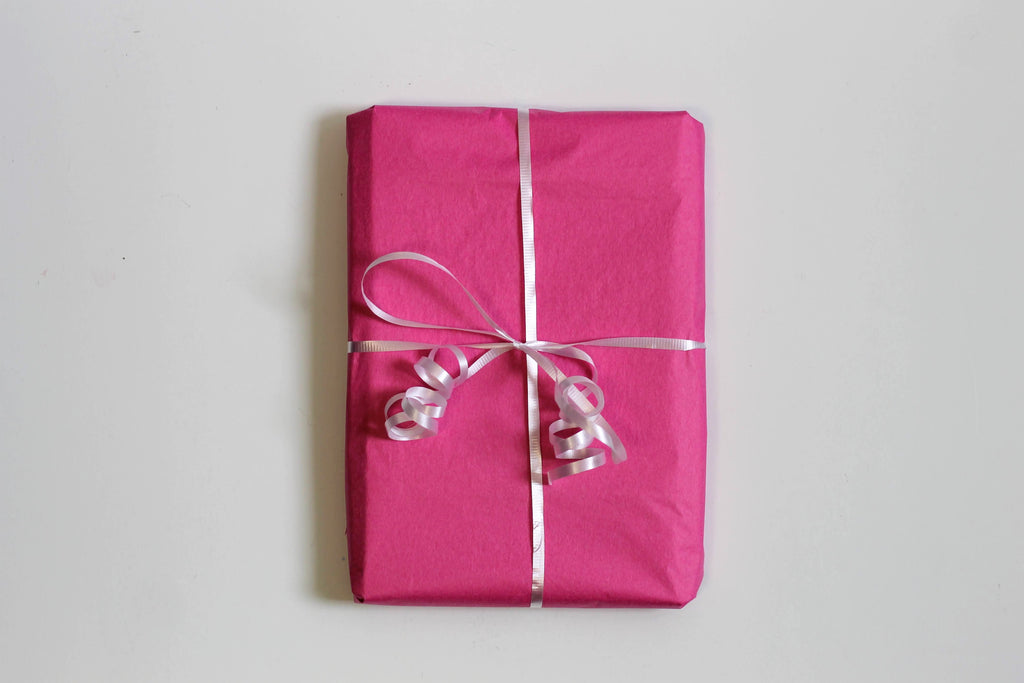 A rectangular package wrapped in pink tissue paper and tied with a white ribbon sits on a white surface.