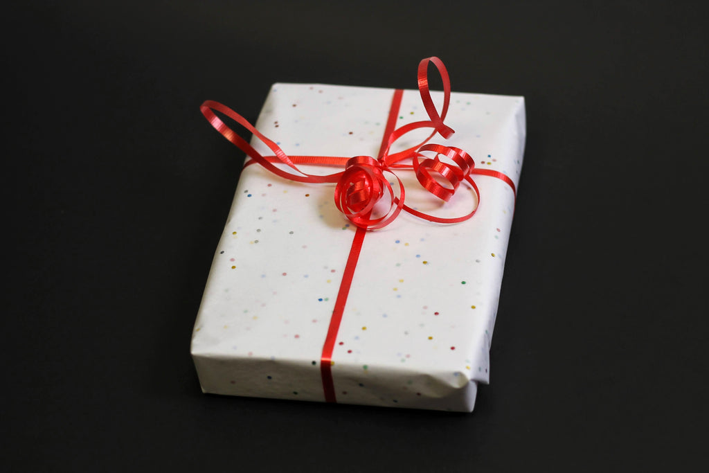 A rectangular package wrapped in white tissue paper dotted with sparkling confetti and tied with a red ribbon sits on a dark surface.