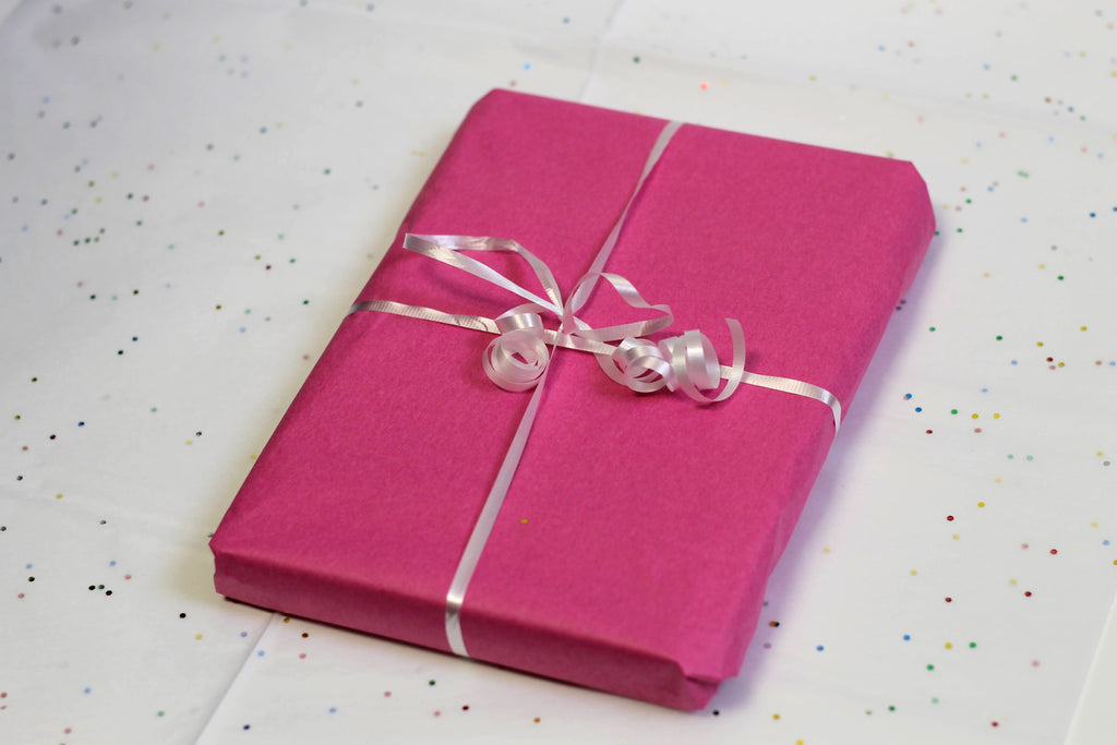 A rectangular package wrapped in pink tissue paper and tied with a white ribbon sits on a white surface dotted with sparkling confetti.