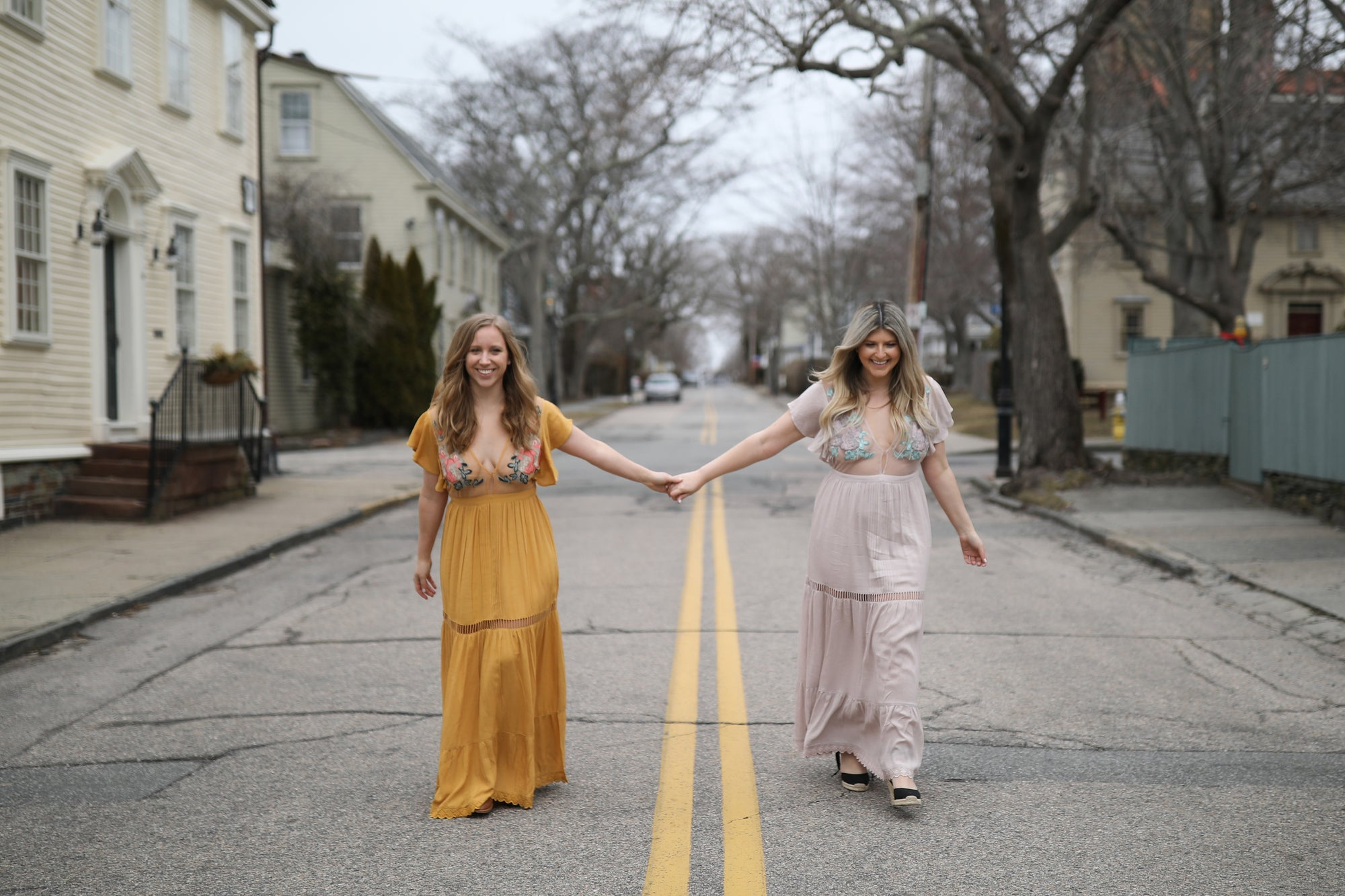 two girls holding hands walking down the street in cleobella amery dresses
