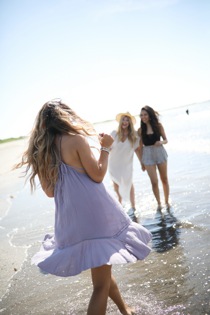 girls frolicking on beach in beach dresses