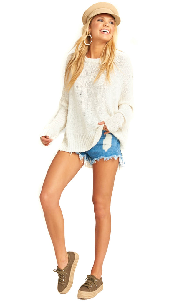 blonde model in cap and white knit sweater and frayed denim shorts