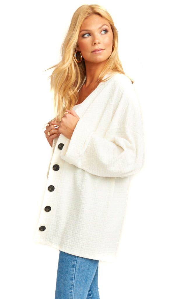 button up white oversized white cardigan draped over light denim