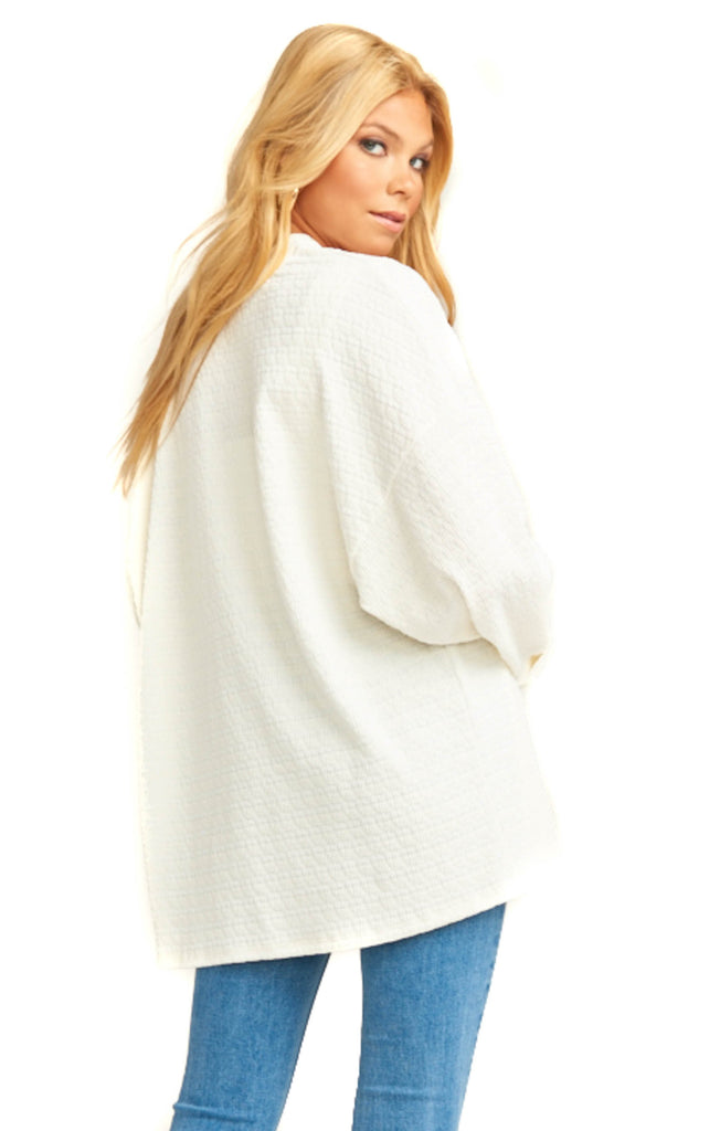 blonde model wearing cream knit cardigan and denim