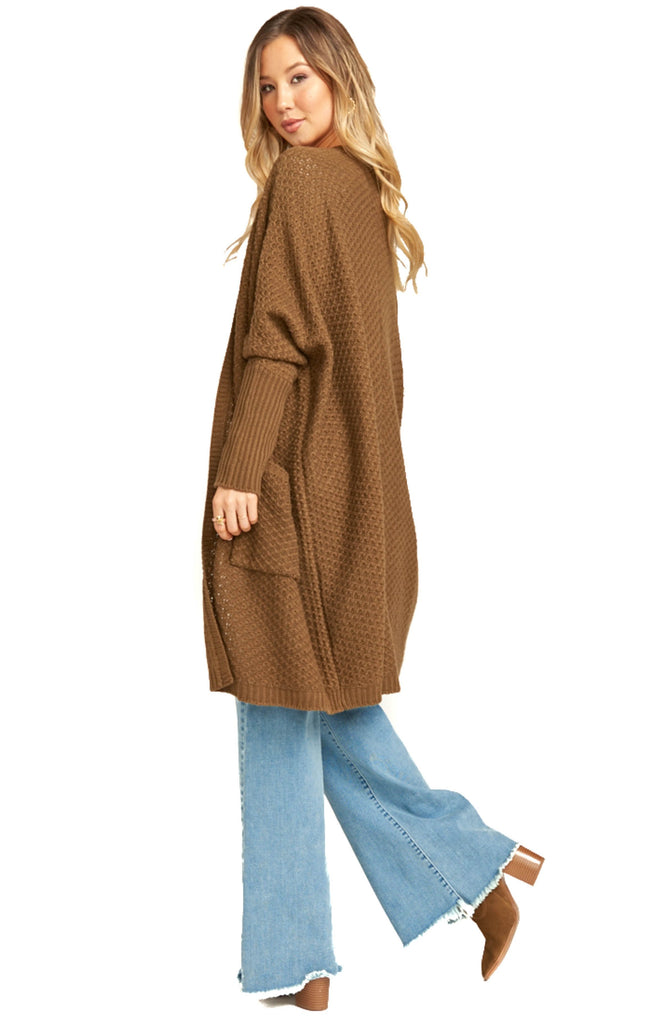 back of show me your mumu oversized chestnut knit cardigan draped over jeans