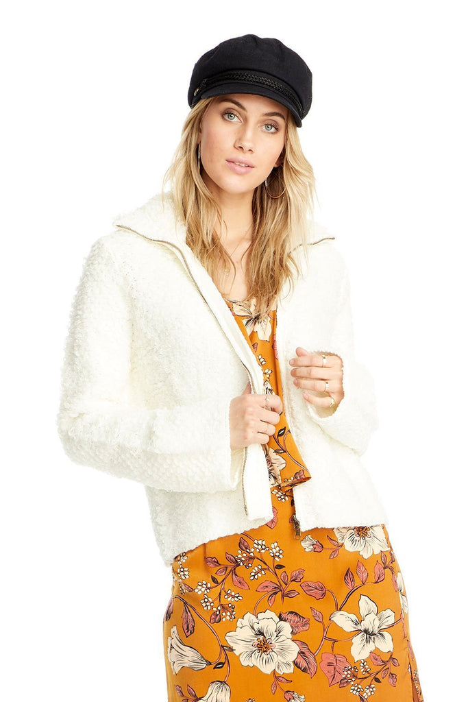woman wearing white shaggy sweater zip up with orange floral dress