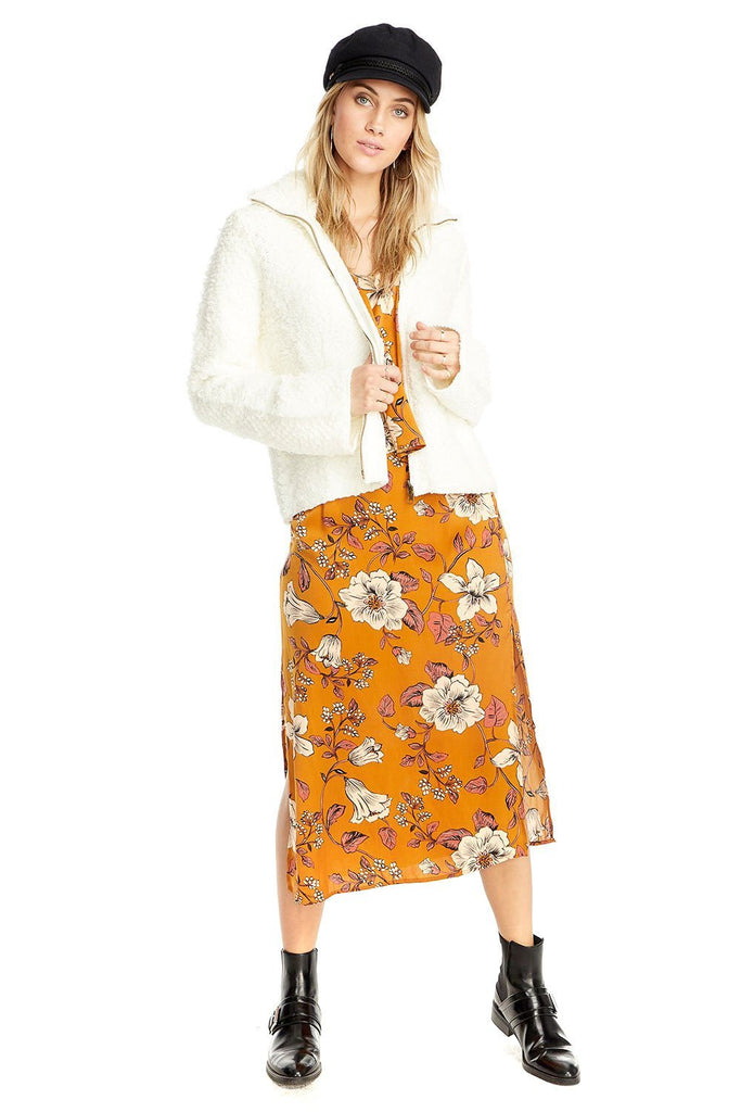 full body photo of white shaggy zip up and orange floral dress
