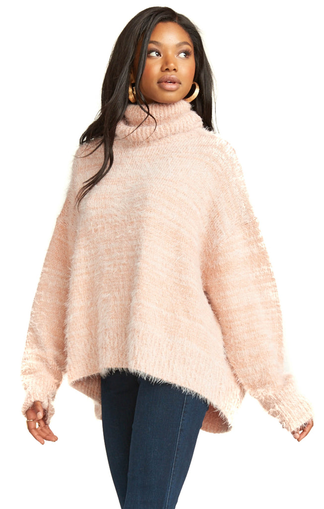 fuzzy pink knit turtleneck with dark denim pants