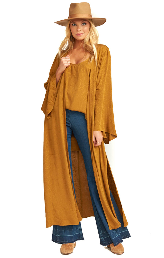 gold Show Me Your Mumu long kimono draped over matching top and denim