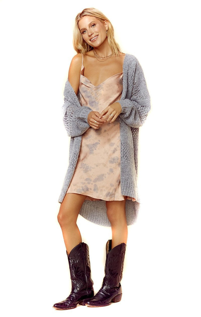 heather grey loose knit cardigan draped over shoulder
